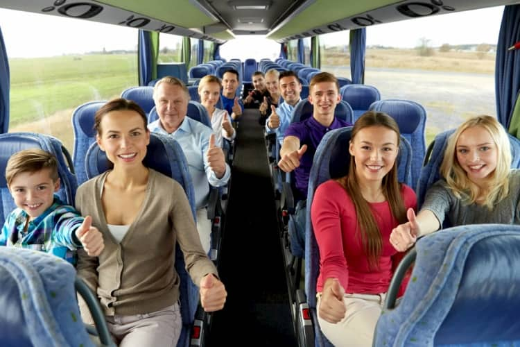 People smiling inside a charter bus