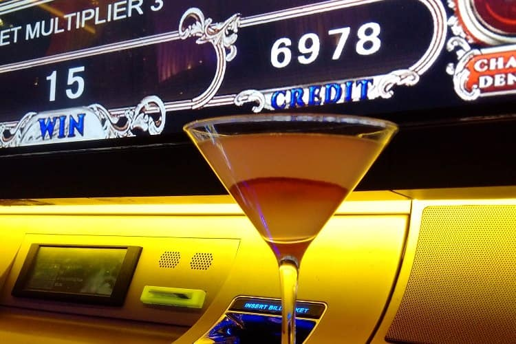 A cocktail placed in front of a slot machine