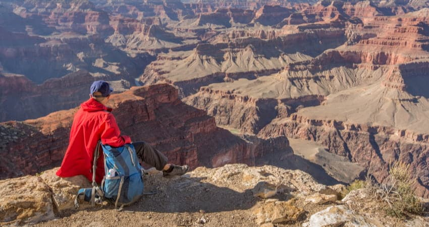 a hiker looks out across the Grand Canyon in Arizona