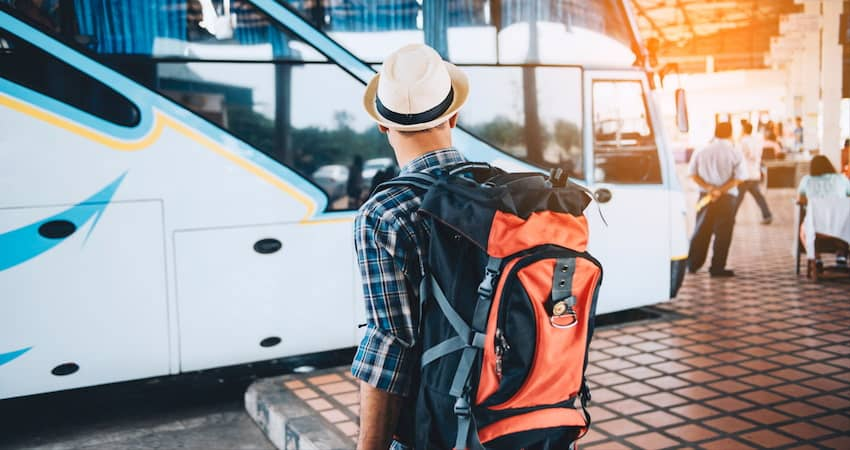 a camper with a backpack prepares to board a private charter bus