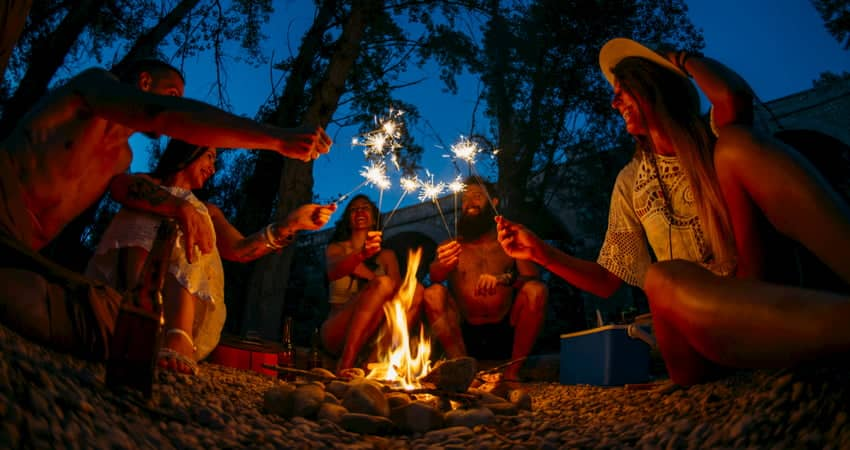 a group of campers come together over a campfire