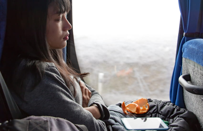 a charter bus passenger takes a nap while on the road