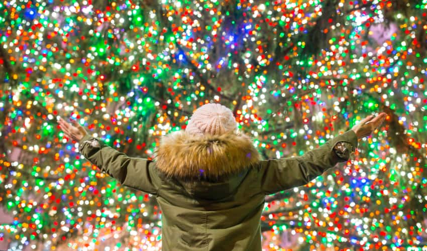 a person in a parka stands with their arms outstretched as a huge christmas tree twinkles in the background
