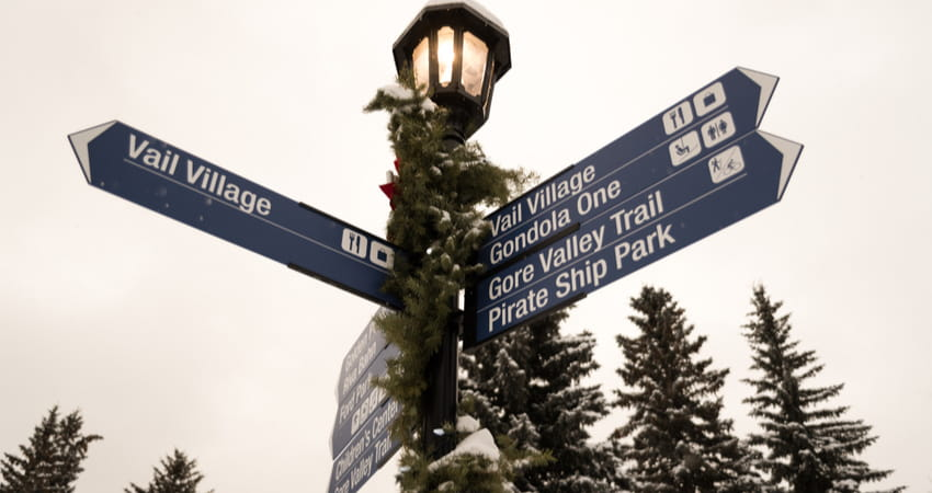 a festive street lamp with signs directing around Vail, Colorado