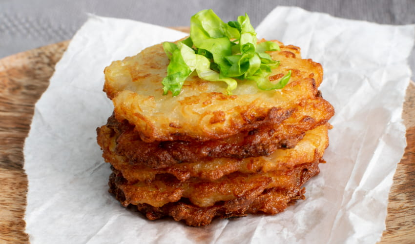 a tall stack of latkes garnished with shredded lettuce