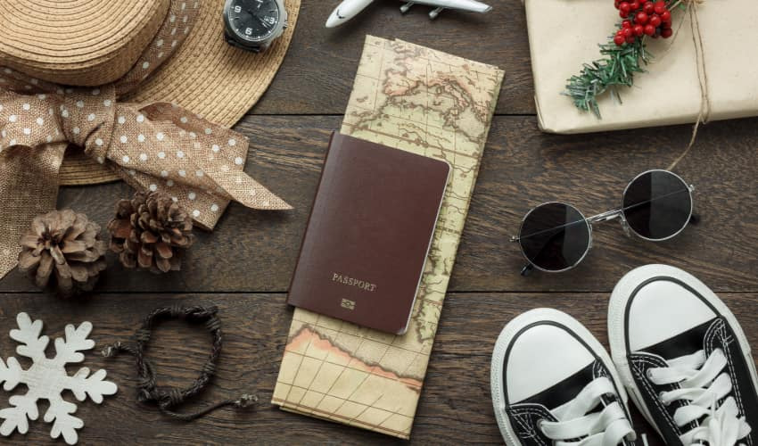 a wooden tabletop with various items spread across it: a wide-brimmed hat, a watch, a model airplane, a wrapped holiday present, sunglasses, a pair of sneakers, pine cones, a snowflake ornament, a map and a passport