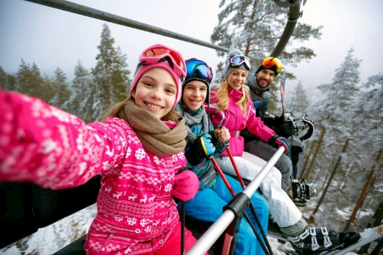 Family taking picture on ski lift