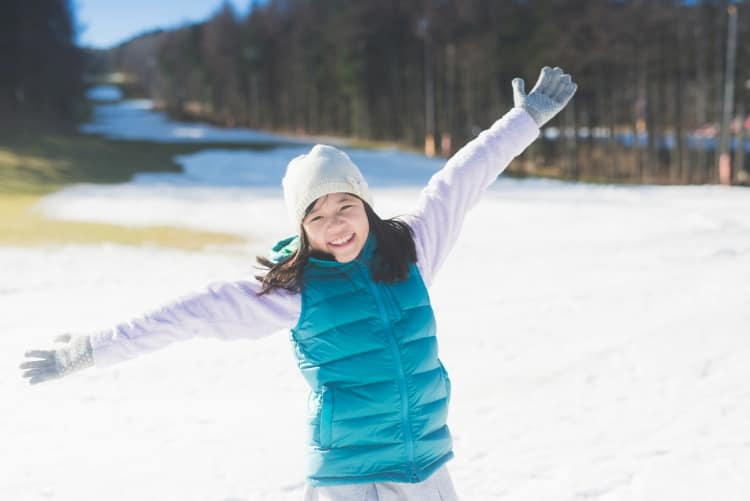 Girl with arms outstretched in snow