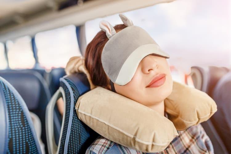 Woman with bunny eye mask sleeping on bus