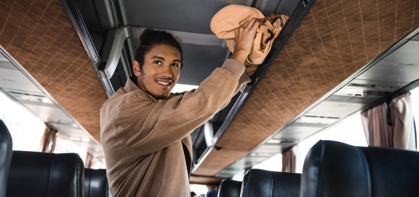 a young man stores his backpack in a charter bus overhead storage bin