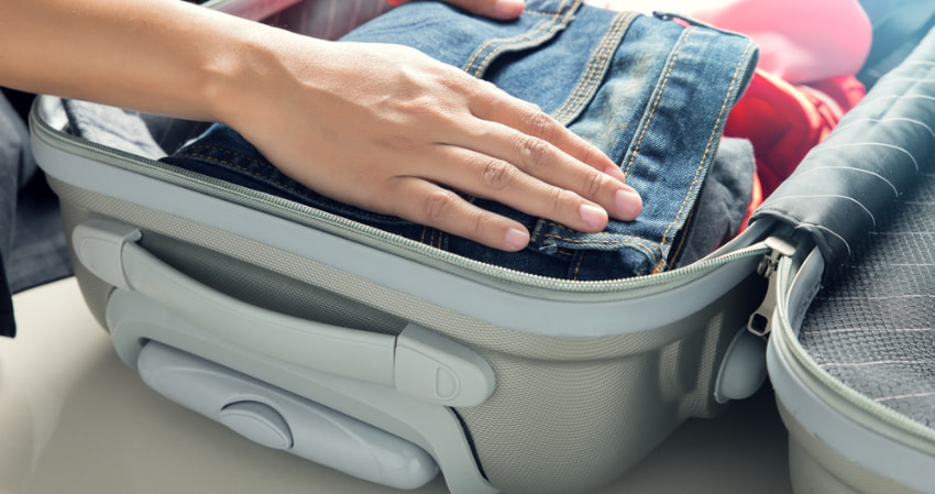 a charter bus passenger packs a suitcase as their carry-on