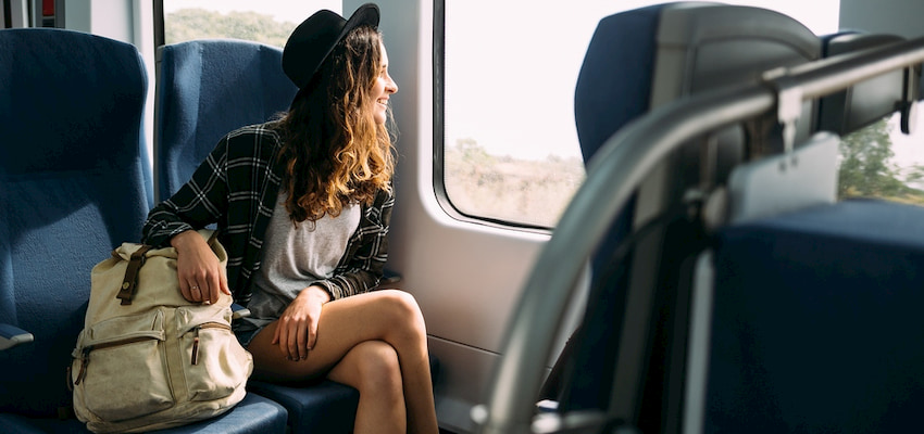 a young woman looks out the window of a charter bus, her carry-on backpack on the seat beside her