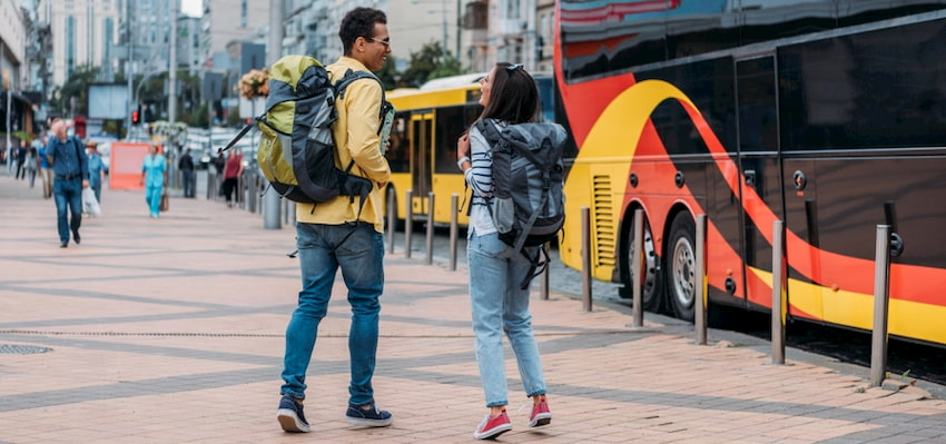 two travelers wait for their charter bus, carry-on bags in hand