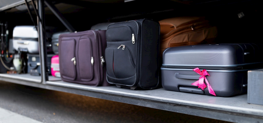 various suitcases in a charter bus luggage bay. one black suitcase has a pink bow tied to the handle
