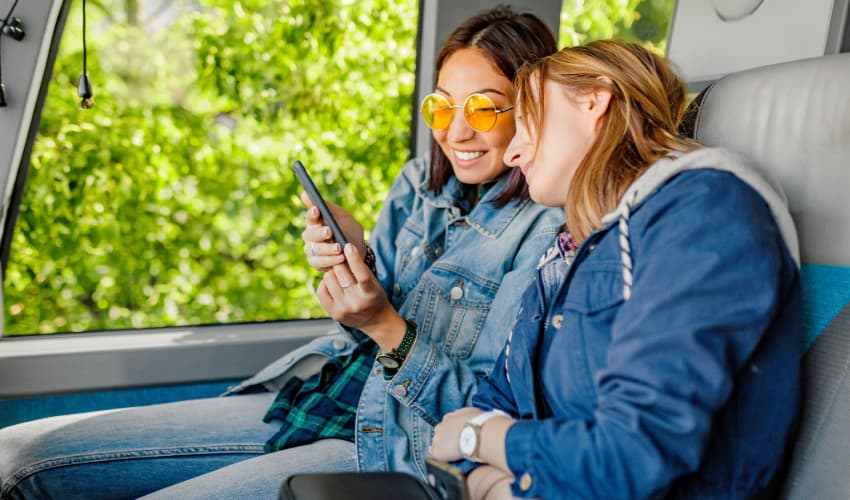 two friends relax on a charter bus, watching a video on a cell phone