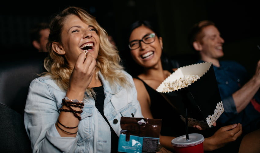 two film enthusaists laugh and share popcorn in a theater