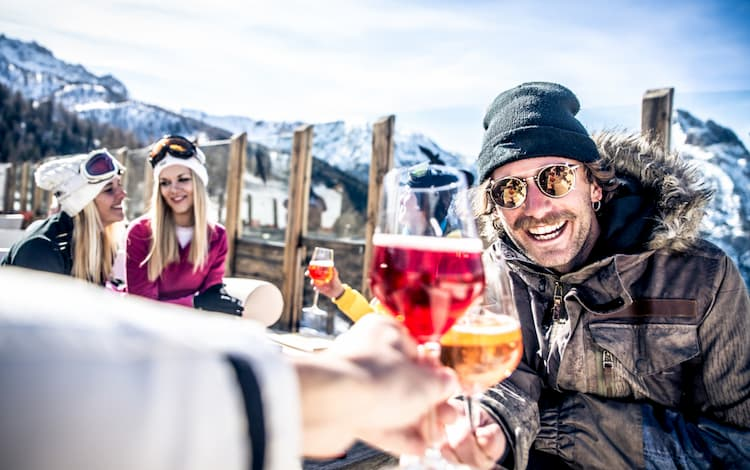 Skiers and snowboarders enjoying a ski trip with wine.