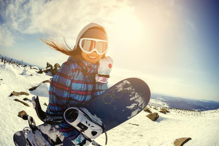 a woman smiles before heading onto a ski slope