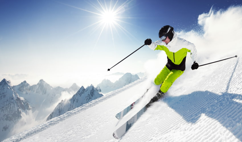 an advanced skier speeds down a powdery slope