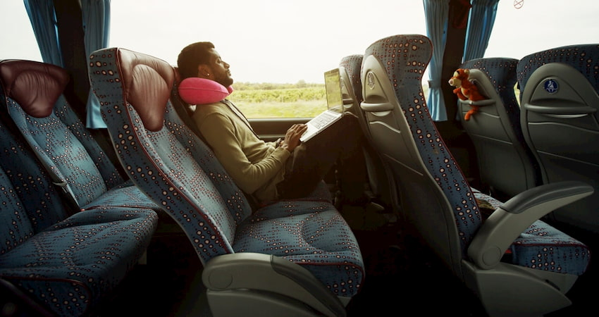 Businessman reclines with a laptop in a Las Vegas charter bus