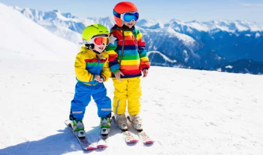 Two children in ski gear on top of a mountain