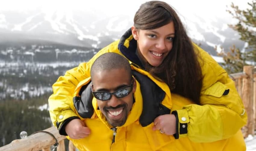 A man and woman on top of a mountain in ski gear