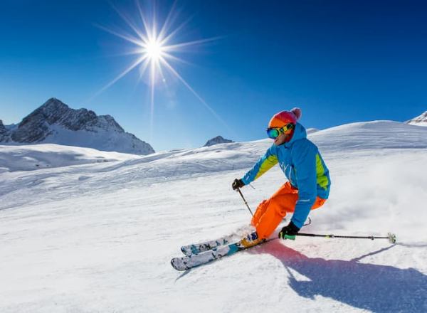 someone in full ski gear slides down a slope with the sun in the background