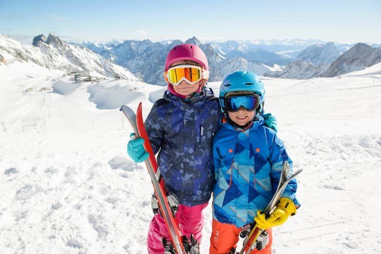 two young kids hold their skis and wear their goggles with snowy mountains in the background