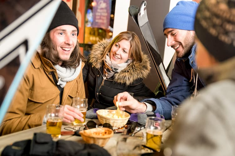 friends enjoy some drinks and snacks at a ski resort before heading back out to the slopes