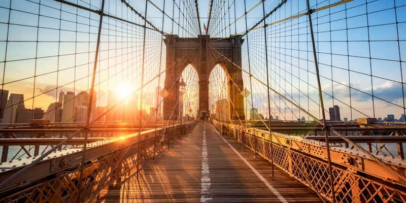 the sun sets over the pedestrian path on the brooklyn bridge in new york city