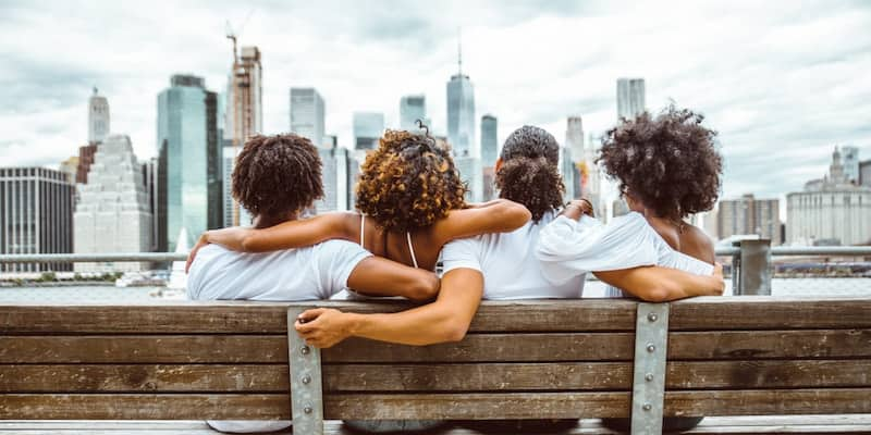 a group of friends sit on a bench in a new york city borough and look at the skyline