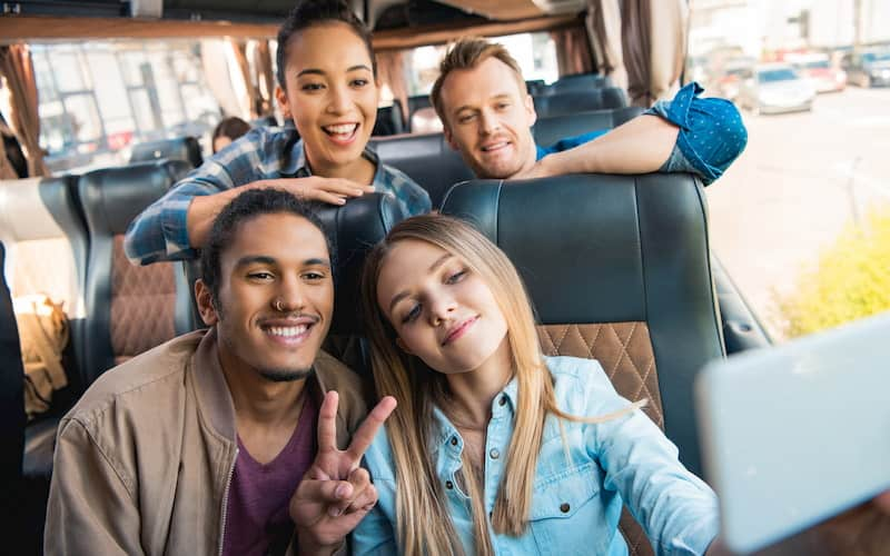 a group of friends ride in a New York City charter bus