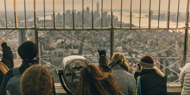 a sightseeing group admires a view on top of the empire state building in new york city