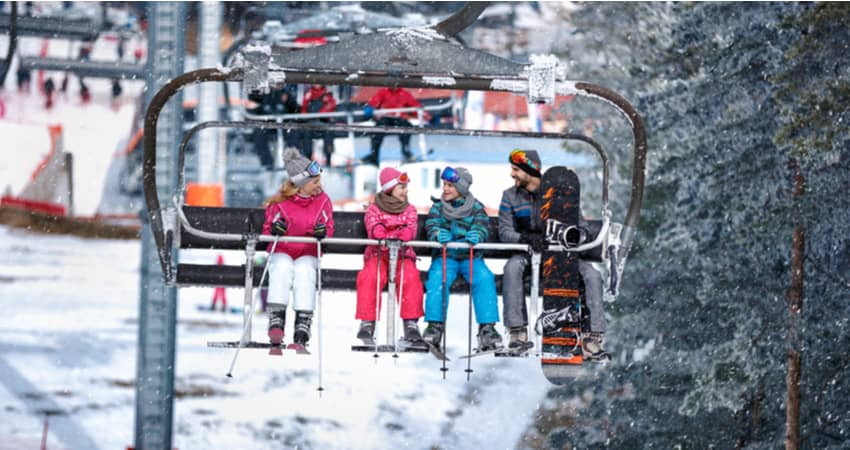 a family with two children riding a ski lift