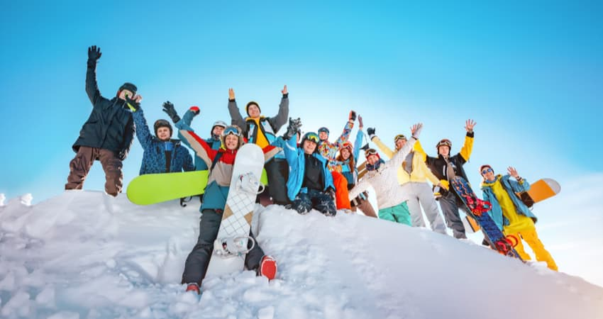 a big group of snowboarders taking a photo at the top of a mountain