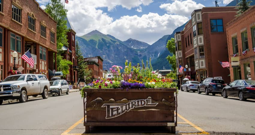 a cart of flowers in the telluride historic district with a mountain peak in the distnace
