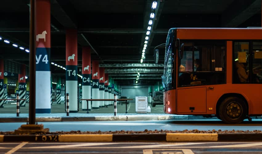 a bus pulls up to a parking deck at night
