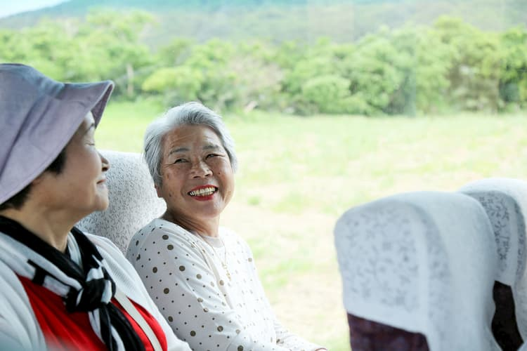 Two older women smiling on charter bus