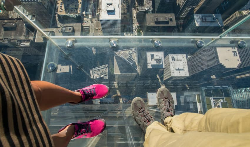 a couple stand on the Skydeck glass viewing platform in Chicago, the street visible beneath them