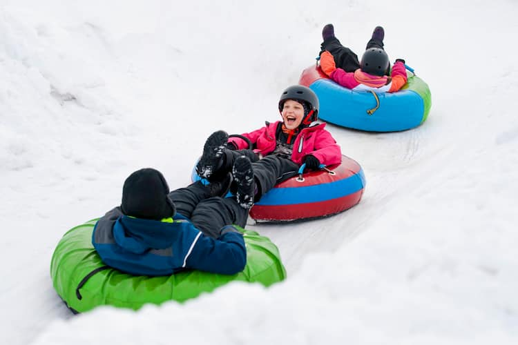 Three kids snowtubing