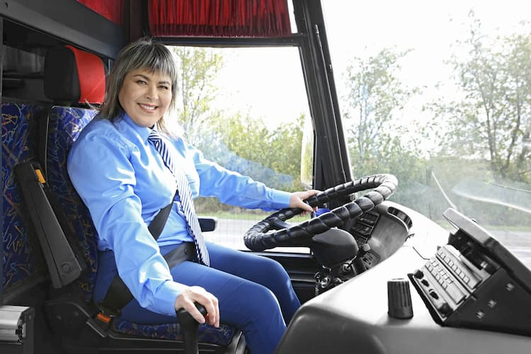 Woman driving bus and smiling
