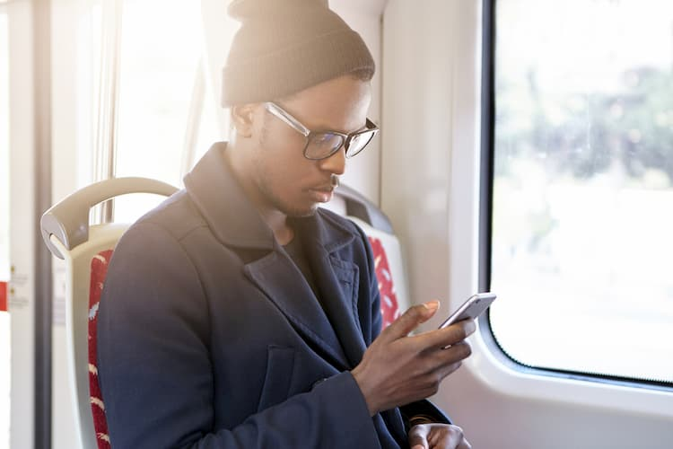 Young man looking at cell phone on bus