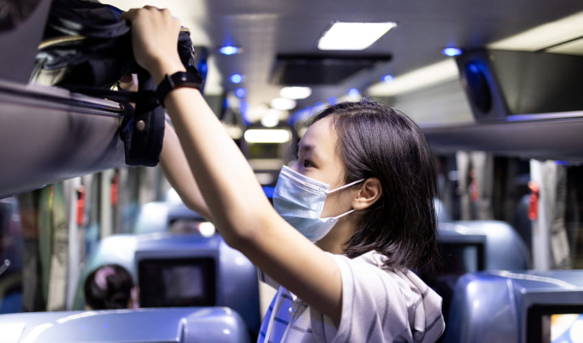 A woman wearing a mask stows her personal bag in the overhead bin of a charter bus
