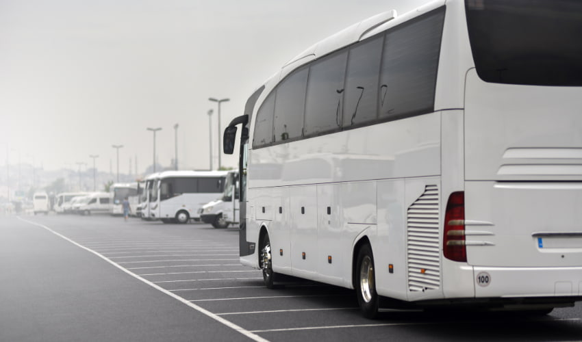 A charter bus parks in a foggy, bus-friendly parking lot
