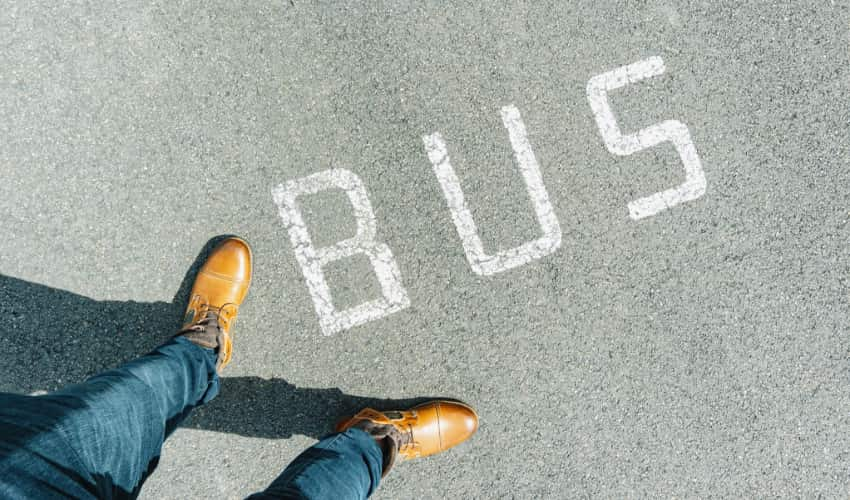 "Top-down view of feet standing new the word ""bus"" painted on a city street"