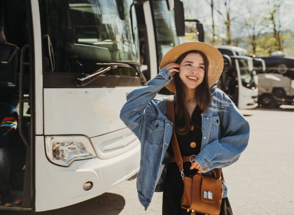 A woman walks by charter buses in a parking lot