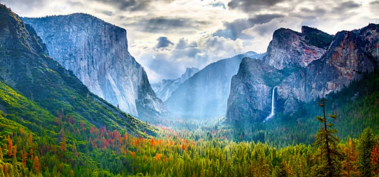 a view of yosemite valley with the sun's rays beaming through the clouds