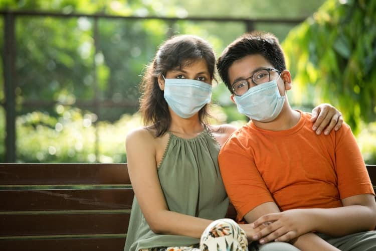Two people sitting on a bench while wearing face masks