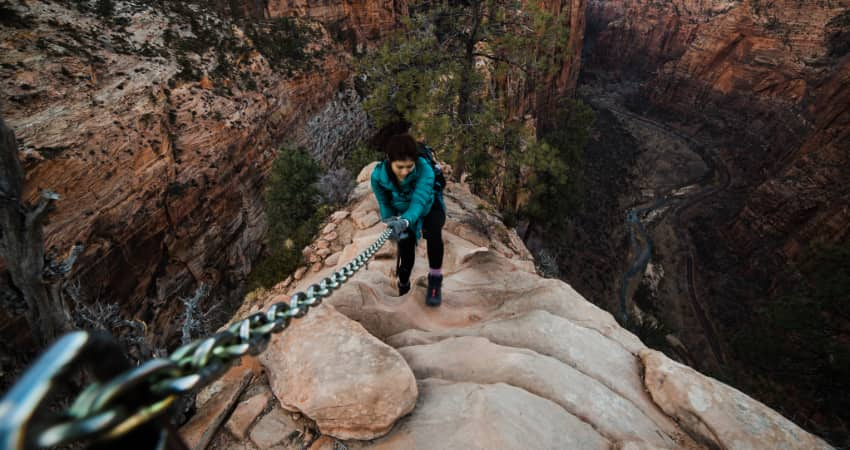 A woman holds on to a chain railing along the narrow ridge of Angel's Landing in Zion National Park