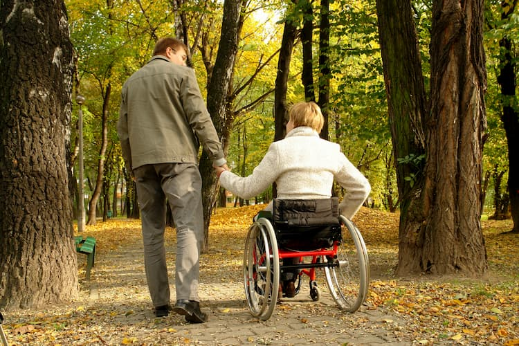 Couple in woods, one in wheelchair, one walking